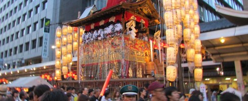 One of the massive parade floats sitting on Shijo dori. The white splotches near the tops are the backs of men ringing many little bells.