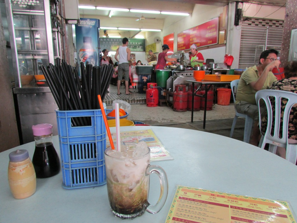Enjoying a cold cendol, a drink with coconut milk, palm sugar and jelly noodles, before my spicy noodles come.